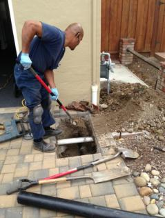 Plumbing contractor removes tiles to access a drain line